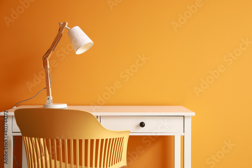 Modern table with lamp and chair near color wall