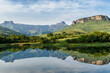 canvas print picture - Mirror like reflection in water of the Amphitheater Drakenberg Mountains in the Royal Natal Nature Reserve in South Africa during green summer.