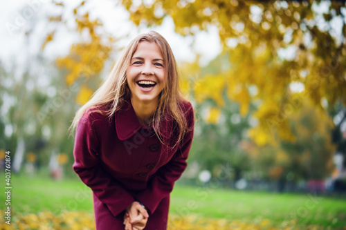Obraz Portrait of happy blonde woman in park in autumn. She is enjoying nature. - fototapety do salonu