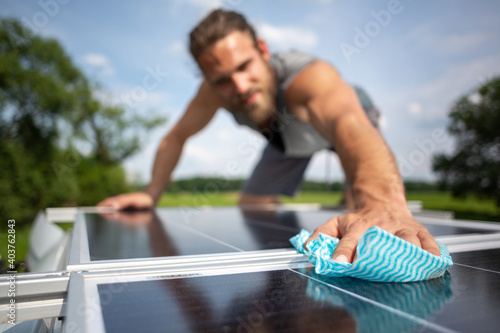 Foto Man wiping a solar panel on the roof of a camper van