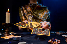 The Fortune Teller Holds A Fan Of Cards In Her Hands And Holds Out A Card With One Hand. Close-up. The Concept Of Divination, Magic And Esotericism