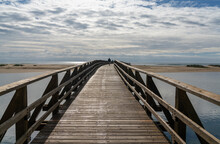 People Crossing Long Wooden Boardwalk To Access La Gaviota Beach In Andalusia