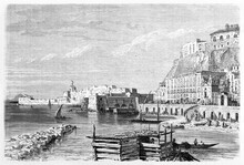 Buildings And Rock Fronting Italian Sea In Borgo Santa Lucia, Historical Quarter Of Naples, Italy. Ancient Grey Tone Etching Style Art Girardet Author, Le Tour Du Monde, 1861