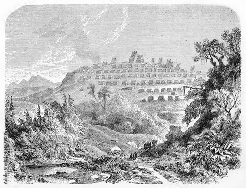 village on a hill far in distance surrounded by luxuriant natural landscape, Tananarive (Antananarivo), capital of Madagascar. Ancient grey tone etching style art by B�rard, Le Tour du Monde, 1861