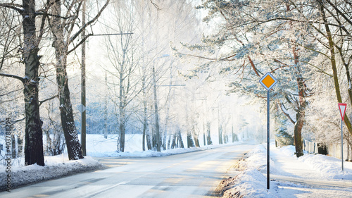 An empty snow-covered asphalt country road (highway) through the pine tree forest at sunset. Road sign close-up. Dangerous winter driving, logistics, remote places. Panoramic image, copy space