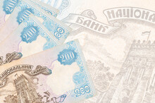 200 Ukrainian Hryvnias Bills Lies In Stack On Background Of Big Semi-transparent Banknote. Abstract Business Background