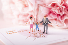 Closeup Of Family Figurines Decorated In Pink Colors Depicting The Mother's Day