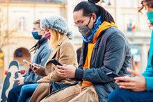 Multiracial Friends Using Mobile Phone Tracking Coronavirus Spread - New Normal Lifestyle Concept With Young People Covered By Face Mask Watching Smartphone.