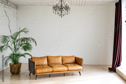 A luxurious large bright living room with a large green potted plant in an industrial style with a brown leather sofa and a brick-and-white wall Fototapet