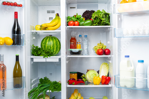 Obraz Open fridge full of fruits, vegetables and drinks - fototapety do salonu