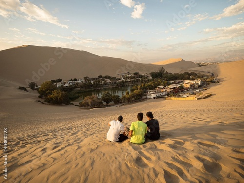 Fototapeta Three friends enjoying panoramic postcard view of Huacachina oasis town village