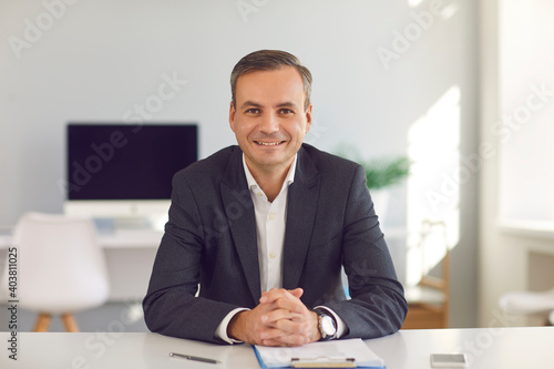 Photo Company's manager sits at a desk in the office and holds an online meeting with his clients