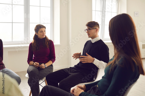 Obraz na plátne Young man talks about his problems or his addiction sitting in a circle during a group therapy session