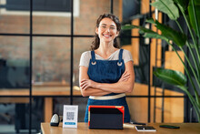 Successful Small Business Owner Standing At Cash Register