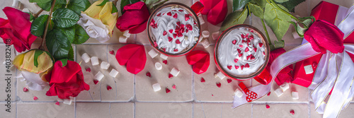 Obraz Valentine hot chocolate or coffee, Two red cups with hot chocolate or latte drink, with whipped cream ans sugar heart sprinkles, with roses bouquet ad gift box - fototapety do salonu