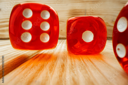 Fotografiet Red dice tossed on wooden background close up