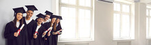 Window Of Opportunity. Hope For The Best Future. Happy Smiling Diverse Academy Graduates Holding Diploma Scrolls. International University Students In Gowns And Caps Celebrating Graduation. Web Banner