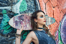 Young Woman With Urban Style, She Poses With A Long Board.