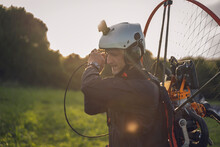 Young Man, With The Powered Paragliding Engine In His Shoulders, Gets Ready To Fly, At Sunset Time, Pulling The Rope To Start The Engine.