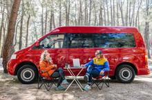 Young Couple Working With Their Laptop Smartphone Outside Campervan