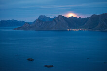 Full Moon Rises Through Thin Clouds Over Mountains And Fjord, Lofoten Islands, Norway
