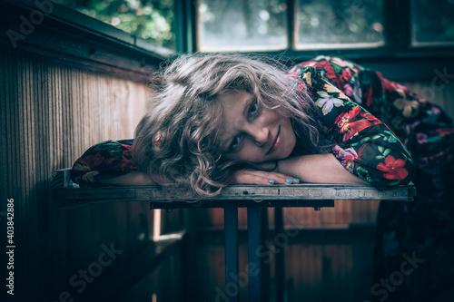 Billede på lærred portrait of girl in colorful dress lying on the table