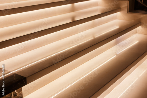 Fototapeta LED illumination of steps of a marble staircase, close up view obraz