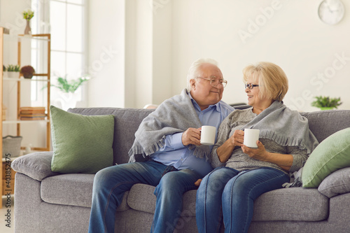 Obraz Smiling mature loving couple grandparents sitting together on sofa under blanket and warming up with hot tea in mugs at home. Elderly people happy lifestyle, family happiness concept - fototapety do salonu
