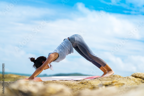 Canvas Print A beautiful woman doing yoga on the rocks at the beachside.