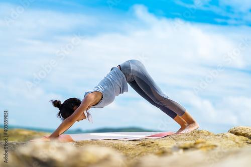 Slika na platnu A beautiful woman doing yoga on the rocks at the beachside.
