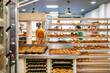Rear view of a bakery with sales clerks selling bread to customers and carts with loaves and cakes fresh from the oven are seen and all are wearing face masks due to the covid19 coronavirus pandemic