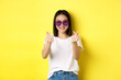 Leinwandbild Motiv Fashion and lifestyle concept. Attractive asian woman in heart-shape sunglasses, showing finger hearts and smiling happy at camera, standing over yellow background