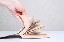 A Hand Flipping Pages Of A Book Lying On A Table, Reading Books Hobby Concept, Learning And Education