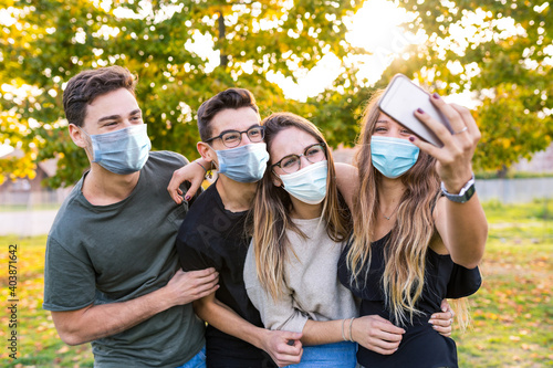 Fotografie, Obraz Teen group of friends together at park after school, wearing masks and taking a