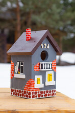 A Hand-painted Bright Birdhouse Close-up Stands On A Wooden Table Outdoors In Winter.