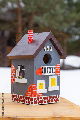 Billede på lærred A hand-painted bright birdhouse close-up stands on a wooden table outdoors in winter