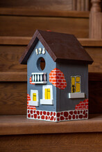 A Hand-painted Vibrant Birdhouse Close-up Stands On The Wooden Staircase Of A House.