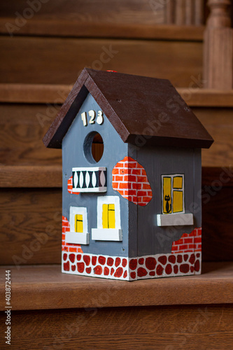 Fotografiet A hand-painted vibrant birdhouse close-up stands on the wooden staircase of a house