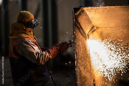 Demolition construction worker using a flame torch to cut up heavy machinery Fotobehang