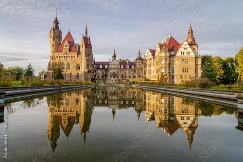 Bajkowy Zamek w Mosznej, lustrzane odbicie w wodzie o wschodzie słońca
