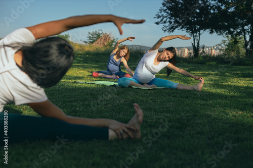 Fototapeta Yoga instructor sitting on the meadow in head to knee yoga position and showing exercises to the pregnant women. obraz