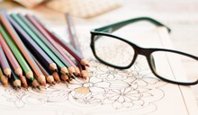 Colored Pencils, Glasses And Coloring Book For Adults