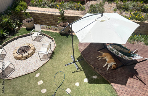 Valokuva Average Australian back yard with umbrella fire pit deck relaxing dog hot summer