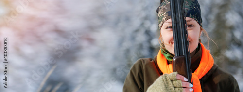 Fotografie, Obraz A young beautiful hunter woman on hunt in forest with rifle on the shoulder