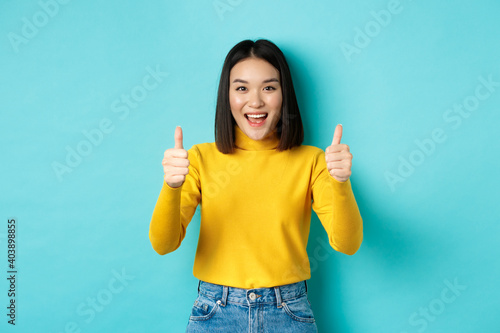 Beautiful asian woman praise good work, showing thumbs up gesture and smiling in approval, recommend product, standing satisfied over blue background