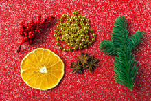 Christmas Decorations Lying Neatly On A Red Background With Sequins. Dried Orange Slice, Sprig Of Fir, Star Anise, Beads With Top View