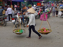 Full Length Of Vendor Selling Fruits On Carrying Pole At Street In City