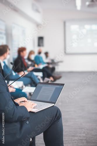 man using a laptop taking notes during a seminar presentation