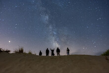 Shot Of A Group Of People Looking At The Starry Night Through Telescopes On Top Of A Sandy Hill