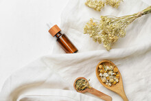 Composition With Different Herbs And Bottle Of Essential Oil On Light Background